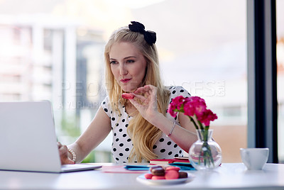 Buy stock photo Shot of a creative young businesswoman eating macarons while using her laptop in the office