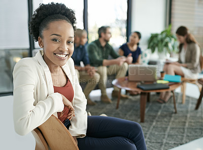 Buy stock photo Portrait of a young businesswoman with her team having a meeting in the background
