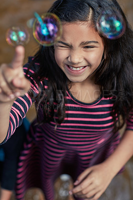 Buy stock photo Shot of a little girl playing with bubbles inside her home