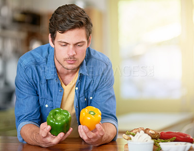 Buy stock photo Shot of a young man deciding which kind or pepper to cook with while standing in the kitchen at home