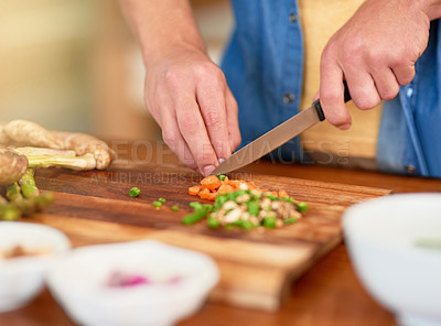 Buy stock photo Closeup shot of a man standing at the kitchen counter chopping up ingredientsfor a meal