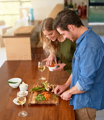 Buy stock photo Shot of a smiling young couple standing at their kitchen counter chopping up ingredients together for dinner