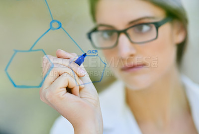 Buy stock photo Closeup shot of a scientist writing formulas on a glass wall