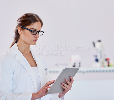 Buy stock photo Shot of a scientist using a digital tablet while standing in a laboratory