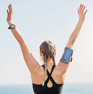 Buy stock photo Rearview shot of an attractive young woman standing with her arms raised after her morning run