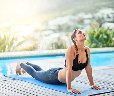 Buy stock photo Shot of an attractive young woman doing yoga outside