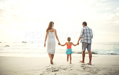 Buy stock photo Shot of two parents walking hand in hand with their little daughter on the beach in the late afternoon
