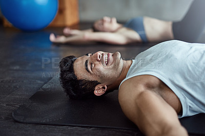 Buy stock photo Shot of two young athletes lying on the floor after a workout in the gym