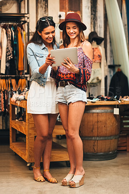 Buy stock photo Shot of two friends using a digital tablet together in a boutique