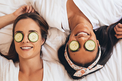 Buy stock photo Shot of two girlfriends relaxing with cucumber slices on their eyes