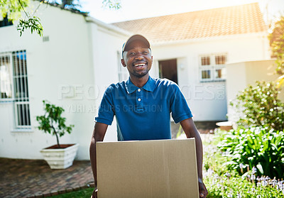Buy stock photo Portrait of a young delivery man carrying a package during a delivery