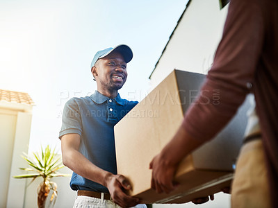 Buy stock photo Shot of a young postal worker delivering a package to a female customer