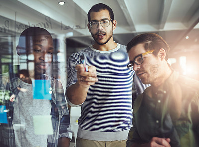 Buy stock photo Cropped shot of a group of young designers planning on a glass board