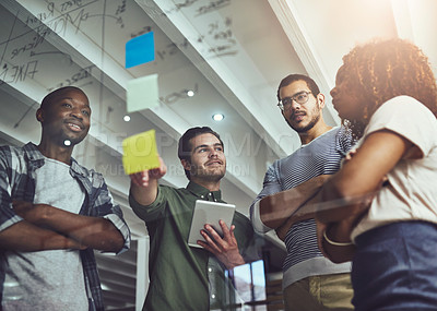 Buy stock photo Low angle shot of a group of young designers planning on a glass board