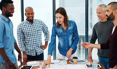 Buy stock photo Cropped shot of a group of architects working on blueprints in the boardroom
