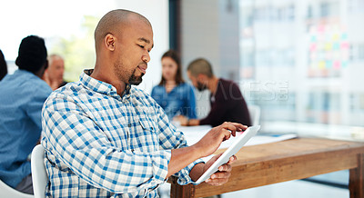 Buy stock photo Shot of a handsome young man using his tablet while sitting in the boardroom during a meeting