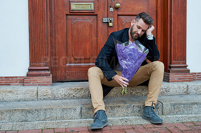 Buy stock photo Shot of a handsome young man looking depressed while waiting with a bunch of flowers on a step