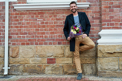 Buy stock photo Portrait of a handsome young man standing against a brick wall with a bunch of flowers in hand