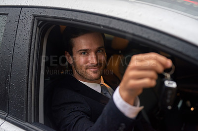 Buy stock photo Shot of a smiling businessman holding keys while sitting in his new car