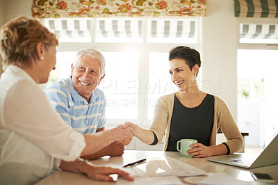 Buy stock photo Shot of a senior couple shaking hands with their financial consultant in their kitchen