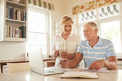 Buy stock photo Shot of a smiling senior couple doing their household finances on a laptop in his kitchen
