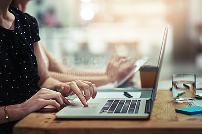 Buy stock photo Cropped shot of an unrecognisable businesswoman working on a laptop in an office