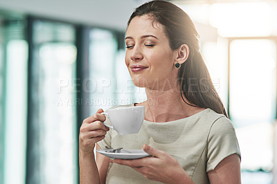 Buy stock photo Cropped shot of a young businesswoman enjoying a cup of coffee in an office