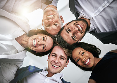 Buy stock photo Portrait of a team of happy colleagues joining huddling together in solidarity