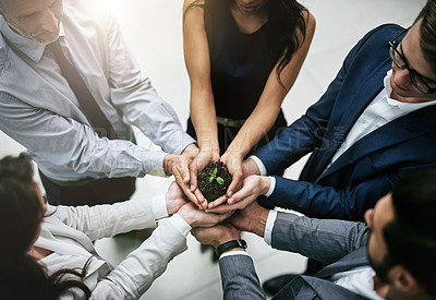 Buy stock photo Cropped shot of a team of colleagues holding a plant growing out of soil