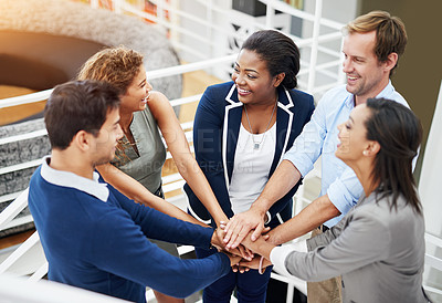 Buy stock photo Shot of a group of coworkers standing with their hands together in a huddle in an office