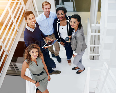 Buy stock photo Portrait of a group of smiling coworkers standing on stairs in a modern office