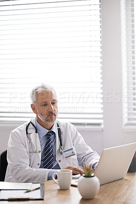 Buy stock photo Cropped shot of a mature male doctor working at his desk