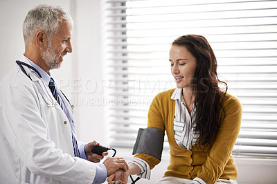 Buy stock photo Cropped shot of a doctor checking a patient's blood pressure