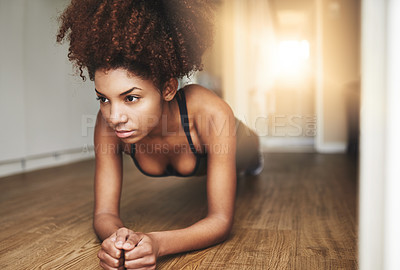 Buy stock photo Shot of a young woman working out at home