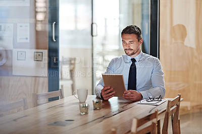 Buy stock photo Shot of a businessman using a digital tablet in an office