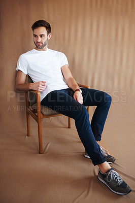 Buy stock photo Shot of a handsome young man sitting on a chair against a brown background