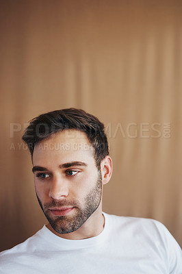 Buy stock photo Shot of a handsome young man posing against a brown background