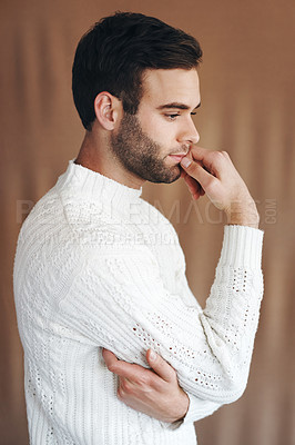 Buy stock photo Shot of a handsome young man looking pensive against a brown background