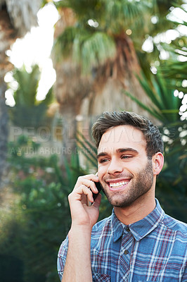 Buy stock photo Cropped shot of a handsome young man making a call while standing outside