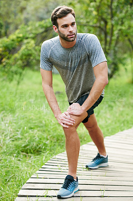 Buy stock photo Shot of a young man stretching before his run in a park