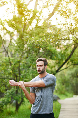Buy stock photo Cropped shot of a young man stretching before his run in a park