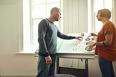 Buy stock photo Shot of two young designers working on a drafting table