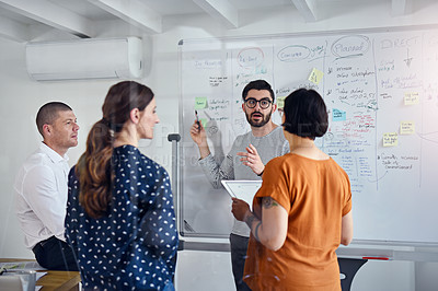 Buy stock photo Cropped shot of a team of professionals brainstorming together on a whiteboard in an office