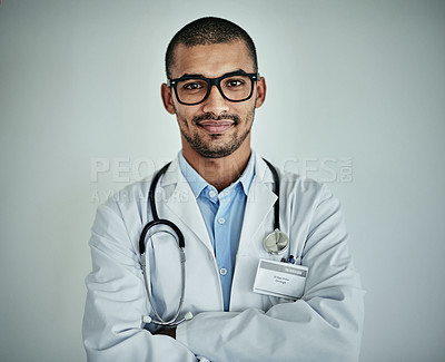 Buy stock photo Studio portrait of a confident male doctor standing against a grey background