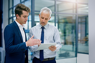 Buy stock photo Cropped shot of two businessmen working together on a digital tablet in an office