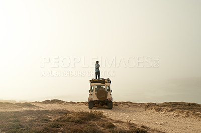 Buy stock photo Shot of a photographer admiring the view while standing on the roof of his off road vehicle