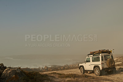 Buy stock photo Shot of an off road vehicle driving toward the ocean on a dirt road