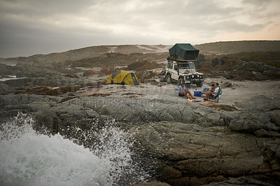 Buy stock photo Shot of a group of friends relaxing by the fire in their campsite by the sea