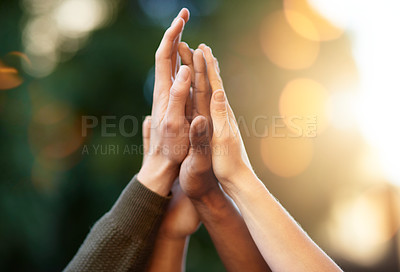 Buy stock photo Cropped shot of a group of people giving each other a high five