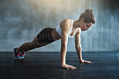 Buy stock photo Shot of a sporty young woman doing pushups at the gym
